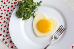 Fried egg in a heart shape with Rocket and fork in a white plate Royalty Free Stock Photo