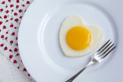 Fried egg in a heart shape in a white plate Royalty Free Stock Images