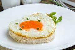 Fried egg heart-shaped Stock Photos