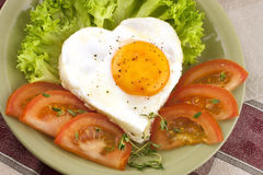 Fried egg on heart-shaped toast with salad Royalty Free Stock Image
