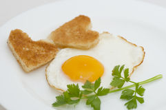 Fried egg with heart-shaped toasts Royalty Free Stock Photography
