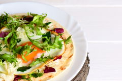 Fried egg, hummus and fresh salad mix on flour tortilla. Tasty tortilla on a plate. Healthy breakfast or lunch idea. Closeup Stock Images