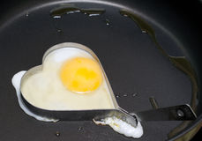 Fried egg in iron form heart crop Stock Photos