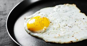 Fried egg in a iron frying pan on Dark stock image