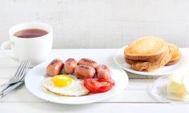 Fried egg, mini sausages, tomato Royalty Free Stock Photo