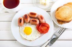 Fried egg, mini sausages, tomato Stock Photo