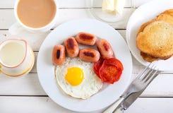 Fried egg, mini sausages, tomato Stock Image