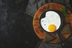 Fried egg in the pan. Dark background, copy space. Toned photo.  royalty free stock image