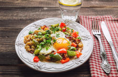 Fried egg with pepper, bacon, potatoes and cilantro Stock Image