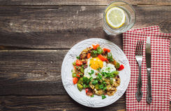 Fried egg with pepper, bacon, potatoes and cilantro Stock Photos