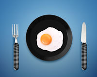 Fried egg on a Plate. Top view of  fried egg on black Plate between silver knife and fork on orange background Stock Photography
