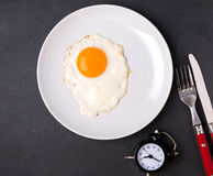 Fried egg on the plate, fork, knife and alarm clock Stock Photos