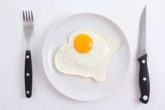 Fried egg in plate with fork and knife over white Royalty Free Stock Images