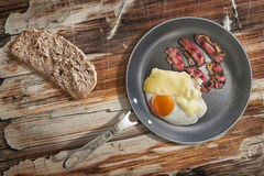 Fried Egg and Pork Ham Rashers In Teflon Frying Pan With Slice Of Brown Bread Set On Old Cracked Wooden Picnic Table Stock Image