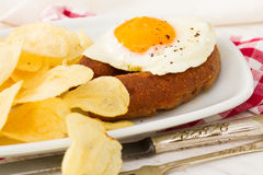 Fried egg with portuguese smoked sausage. And potato chips Royalty Free Stock Photo