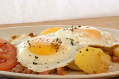 Fried egg with potato and bacon Stock Photos