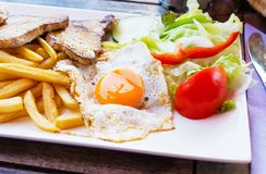 Fried egg with potato fries, grilled steak. Royalty Free Stock Images