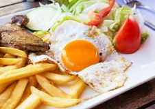 Fried egg with potato fries, grilled steak. Stock Images