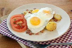 Fried egg with potato and tomato Stock Photos