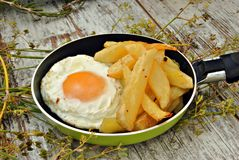 Fried egg with potatoes, served in a pan Stock Photography