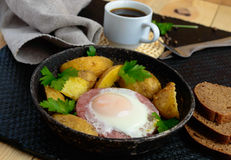 Fried egg in salami and baked potatoes. Submission of a frying pan with a cup of coffee and rye bread. Breakfast royalty free stock images