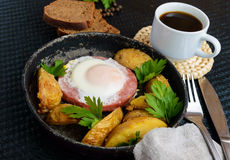Fried egg in salami and baked potatoes. Submission of a frying pan with a cup of coffee and rye bread. Breakfast.  stock photos