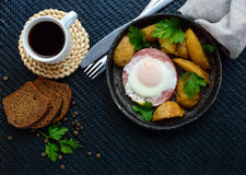 Fried egg in salami and baked potatoes. Submission of a frying pan with a cup of coffee and rye bread. Breakfast. The top view stock photo