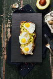 Fried egg sandwich: quail eggs, avocado and cheese on whole whea. T bread Stock Photo