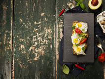 Fried egg sandwich: quail eggs, avocado and cheese on whole whea. T bread Royalty Free Stock Photography