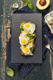 Fried egg sandwich: quail eggs, avocado and cheese on whole whea Royalty Free Stock Photo