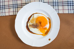 Fried egg with sauce on dish Stock Images