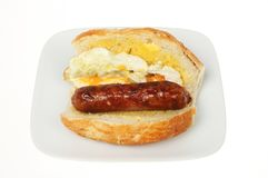 Fried egg and sausage giraffe roll. Fried egg and sausage in a giraffe bread roll on a plate isolated against white royalty free stock photo