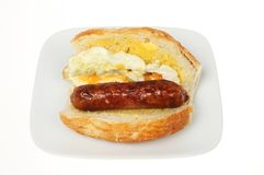 Fried egg and sausage giraffe roll. Fried egg and sausage in a giraffe bread roll on a plate isolated against white Royalty Free Stock Photography