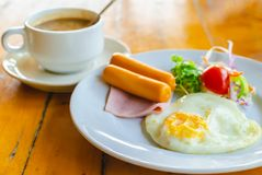 Fried egg with sausage and ham served with vegetable salad and hot coffee for appetizing breakfast.  royalty free stock photo