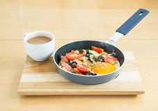 Fried egg with sausage in a pan and  hot coffee on wooden table Royalty Free Stock Photography