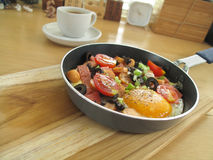 Fried egg with sausage in a pan and  hot coffee on wooden table Stock Image