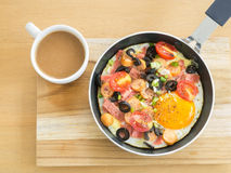 Fried egg with sausage in a pan and  hot coffee on wooden table Royalty Free Stock Images