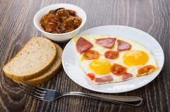Fried egg with sausage in plate, bread, eggplants in bowl Royalty Free Stock Photos
