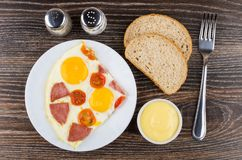 Fried egg with sausage in plate, bread, salt, pepper, mayonnaise Royalty Free Stock Photo