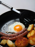 Fried egg, sausage, potato breakfast frying pan Stock Photos