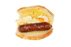 Fried egg and sausage roll. Fried egg and sausage in a giraffe bread roll isolated against white royalty free stock photo