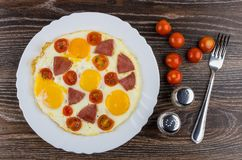 Fried egg with sausage and tomatoes in dish, salt, pepper. Fried egg with sausage and tomatoes in white dish, salt, pepper and fork on wooden table. Top view Stock Images