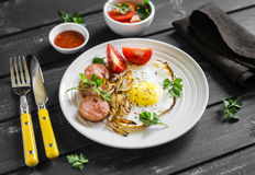 Fried egg, sausage, tomatoes - tasty Breakfast or snack, on the bright plate Stock Images