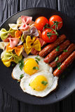 Fried egg, sausages, pasta farfalle and tomato close-up. Vertica Royalty Free Stock Image