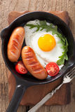 Fried egg sausages tomatoes in pan for breakfast Royalty Free Stock Images