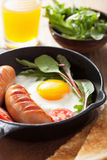 Fried egg sausages tomatoes in pan for breakfast Stock Image
