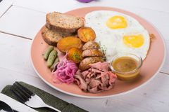 Fried egg served with pastrami stock image