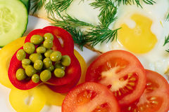 Fried egg - serving. Fried egg, garnished with slices of juicy tomatoes and green peas stock photo