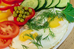 Fried egg - serving on a plate. Fried egg, garnished with slices of tomatoes, cumumber and green peas royalty free stock photo