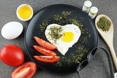 Fried egg in shape of heart on black plate. Royalty Free Stock Photo